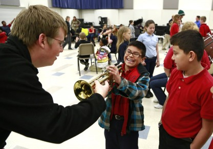 Butler student Paul Belleville lets some Indianapolis Public Schools students hold his trumpet.