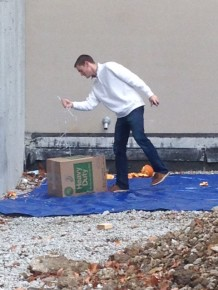 Gone... Ryan Krueger collects one of the pumpkins after its fall from the parking garage roof.
