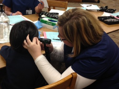 Emily Williams checks a Lab School student's ear for excessive wax.