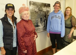 Jan Conner Wahls, in pink hat, portrayed women's rights crusader May Wright Sewall in two Butler classes Oct. 16. With her, from left, are students Bethany Feitshans and Carly Allen, and instructor Ann O'Connor-Ledbetter.