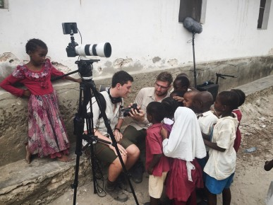Timothy Valentine and Joshua Gaal show their cameras to children in Kenya.